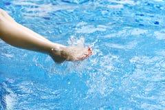 Tyck om den härliga flickan som kopplar av i simbassängen, ben av kvinnan i vatten royaltyfri fotografi