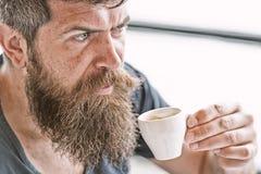 Tyck om den varma drinken Hipster som dricker utomhus- kaffe Man med sk?gget och mustasch och kopp kaffe Sk?ggig grabb som koppla arkivbild