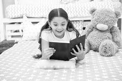 Tyck om det favorit- ögonblicket Flickabarnet lägger säng med den lästa boken för nallebjörnen Ungen förbereder sig att gå att bä arkivbild