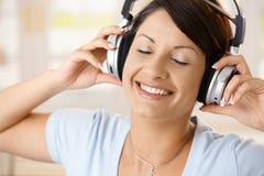 tycka om den lyckliga hörlurarmusikkvinnan Royaltyfri Bild