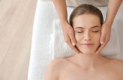 Tycka om för ung kvinna av den ansikts- massagen royaltyfri fotografi