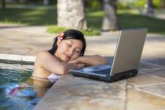 Tycka om ferie med bärbara datorn i pölen arkivfoto