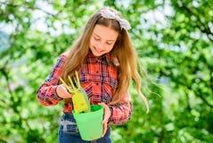 Tycka om hennes arbete med v?xter v?rbyland liten flickaunge i skogliten flicka med att arbeta i trädgården hjälpmedel arkivfoto