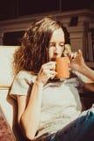 tycka om home tid Stäng sig upp den kastanjebruna hårkvinnan för ståenden som kopplar av i bekväm stol på fönstret som dricker te Royaltyfria Foton