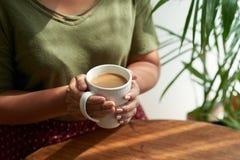 Tycka om kaffe på det hemtrevliga kafét Arkivbild