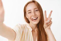 Tycka om kalla sommarferier Stilfull härlig rödhårig mankvinna med gulliga fräknar som ut klibbar tungan och grinar från arkivbild