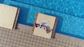 Tycka om sommar, ligger den flyg- sikten av unga flickan i baddräkt på near pöl för terrass med blått härligt vatten stock video