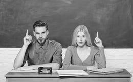 Tycka om universitetliv Grabben och flickan sitter p? skrivbordet i klassrum Korrekt svar p? deras mening Studera i h?gskola elle fotografering för bildbyråer