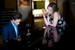 Tyckande om och beundra för man leka piano för kvinna Royaltyfria Foton