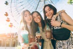 Tycker om blandras- kvinnor för sommarlivsstilstående den trevliga dagen, hållande exponeringsglas av milkshakar Lycklig vänininf arkivfoton