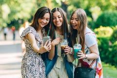 Tycker om blandras- kvinnor för sommarlivsstilstående den trevliga dagen, hållande exponeringsglas av milkshakar Lyckliga vänner  arkivfoton