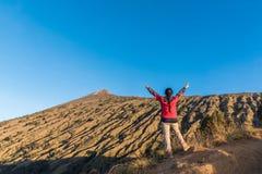 Tycker om den fördelande handen för kvinnafotvandraren, och lyckligt med bästa sikt för berg efter färdig klättring på monteringe royaltyfri bild