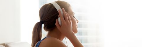 Tycker om den kvinnliga bärande hörlurar för sidosikt favorit- musik hemma royaltyfria foton
