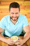 Tycker om den lyckliga framsidan för kafébesökaren kaffekoffeindrinken Mannen uppsökte grabben dricker cappuccino på trätabellkaf arkivfoto