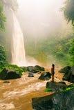 Tycker om den sexiga kvinnan för ung skönhet den spektakulära morgonsikten, den härliga Nungnung vattenfallet, Bali royaltyfria bilder