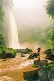 Tycker om den sexiga kvinnan för ung skönhet den spektakulära morgonsikten, den härliga Nungnung vattenfallet, Bali arkivbild
