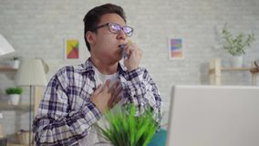 Tycker om den unga asiatiska mannen för ståenden i en skjortaastmatiker sprejen från att hosta att sitta på bärbara datorn stock video
