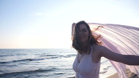 Tycker om hållande ljust tyg för den härliga kvinnan på stranden och solnedgången arkivfilmer