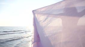 Tycker om hållande ljust tyg för den härliga kvinnan på stranden och solnedgången stock video