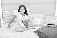 Tycker om långt lockigt hår för flickan aftontid med den favorit- leksaken Ungen sitter säng och spelar inre för sovrummet för ka royaltyfria bilder