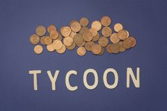 Tycoon written with wooden letters on a blue background. To mean a business concept Royalty Free Stock Images