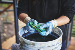 Tye dying fabric. A woman dying fabric with indigo dye using bamboo and rubber bands royalty free stock images