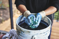 Tye dying fabric. A woman dying fabric with indigo dye using bamboo and rubber bands stock photo