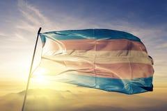 Tyg för torkduk för textil för Transgenderstolthetflagga som vinkar på den bästa soluppgångmistdimman royaltyfri foto