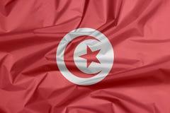 Tygflagga av Tunisien Veck av tunisisk flaggabakgrund arkivfoton