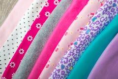 Tygsömnad Vikt rosa och vit bodysuit på den grå träbakgrund blöja för nyfödd flicka Bunt av begynnande kläder CH royaltyfri bild