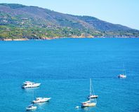 Tyhrrhenian sea, hills, boats, mountains, Tuscany, in Elba island, Italy. Boats in Capoliveri beach, mountains and hills in Tuscany, in Italy. Beautiful gaze of Royalty Free Stock Photography
