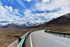 Tyibet lång väg framåt med det främsta höga berget Arkivfoto