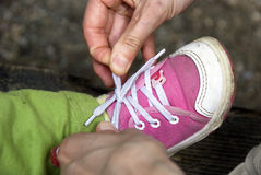 Tying baby shoes royalty free stock images