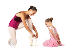 Tying ballet shoes. Young female ballet dancer showing a young dancer how to tie a ballet Pointe Shoe against a white background. NOT ISOLATED stock photo