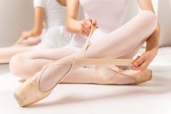 Tying ballet slippers. Close-up of ballerina in white tutu tying her slippers while sitting near the mirror royalty free stock image