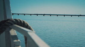 Tying Boat Ropes with a Bridge under the Sea on the Background. Close up of boat ropes in the sea stock footage