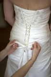 Tying bow on wedding dress Stock Images