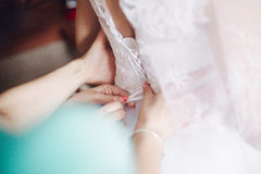Tying the bride dresses. Bridesmaid tying bow on wedding bride dress Stock Images