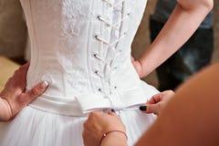 Tying corset of dress bride Stock Photos