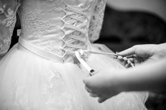 Tying a corset to bride. Tying on a white corset bride Stock Photography