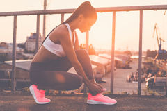 Tying her shoelaces. Beautiful young woman in sports clothing tying her shoelaces while standing on the bridge with evening sunlight and urban view in the royalty free stock images