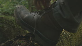 Tying hiking boot shoe laces Man Hiking Through A Forest Outdoors Day. Tying hiking boot shoe laces Man Hiking Outdoors With Rucksack Backpack Walking In stock footage