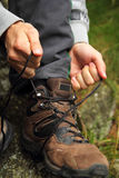 Tying hiking boots. Tying boots in nature - hiking concept stock photo
