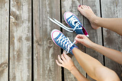 Tying laces of jeans sneakers on the wooden floor Stock Photography