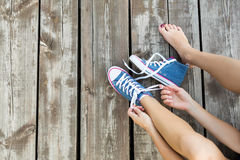 Tying laces of jeans sneakers on the wooden floor Stock Image