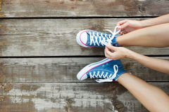 Tying laces of jeans sneakers on the wooden floor Stock Photos