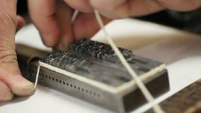 Tying letterpress type before printing. Letterpress printer secures metal type with string stock video