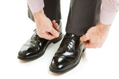 Tying New Shoes. Closeup of a mans hands as he ties his shiny new dress shoes.  Isolated on white Royalty Free Stock Photo