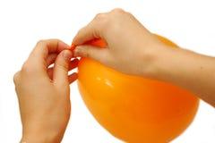 Tying orange balloon Royalty Free Stock Image