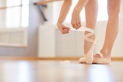 Tying pointe shoes ribbon stock image